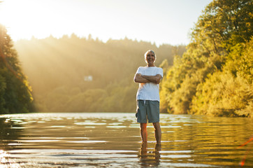 Portrait of a smiling senior man standing next to a lake while on vacation.