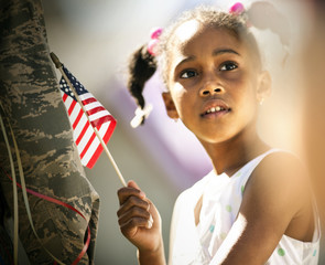 Thoughtful young girl holding an American flag while standing next to someone in a military uniform.