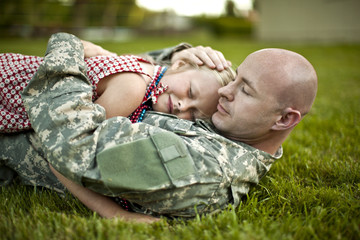 Male soldier hugging his young daughter while lying on the grass in their back yard.