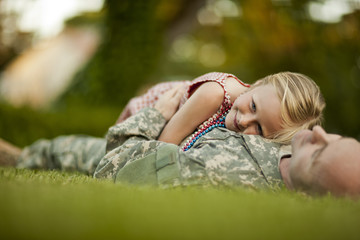 Male soldier and his young daughter while lying on the grass in their back yard.