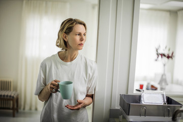 Woman drinking coffee in kitchen.