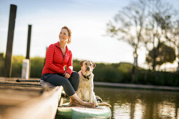 Mid adult woman sitting on wharf with pet golden labrador.