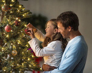 Happy father and daughter decorating a Christmas tree together.