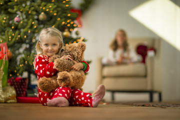 Portrait of a young girl hugging her teddy bear on Christmas morning.