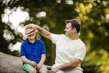 Smiling father playfully placing a straw hat on his son's head.