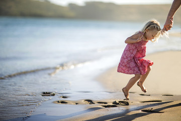 Happy young girl playing in wet sand at low tide.