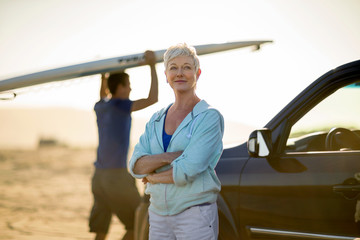 Portrait of a content mature woman standing by her car.