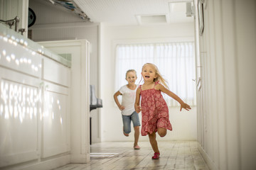 Two little girls have fun running through the house together.