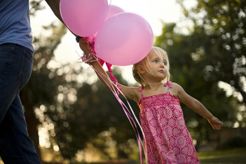 Young girl holding pink balloons and her father's hand.