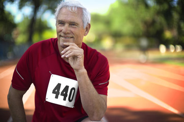 Portrait of a smiling mature man crouching down on an athletic track.