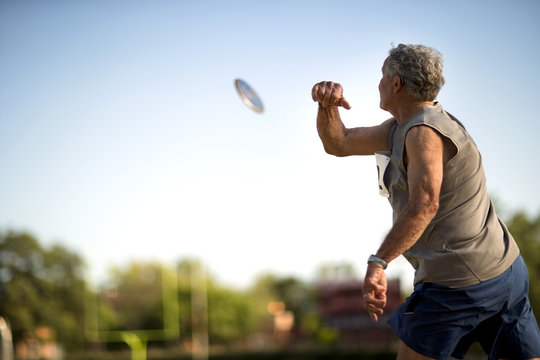 Mature man throwing a discus during an athletics event.