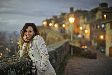 Portrait of a smiling young woman leaning on a stone wall at dusk.