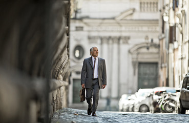 Successful mature businessman walking down a cobblestone street.