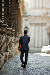 Young businessman makes a call as he strolls along a city street.
