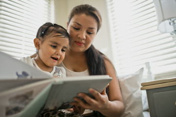 Mother and daughter reading a book together.