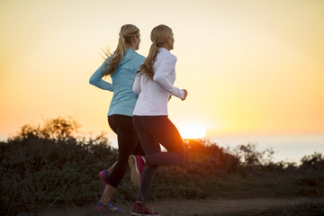 Two young women go for a sunrise jog together along the cliff tops by the ocean.