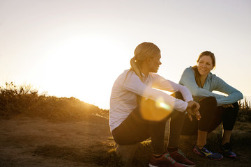 Two young women take a break from their sunrise jog along the cliffs to sit and have a cheerful discussion.
