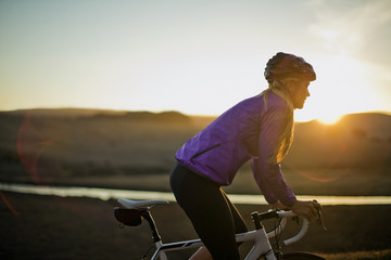 Young woman cycling down a country road at sunset.