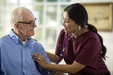 Smiling senior man having a conversation with a female nurse as she listens to his heartbeat through a stethoscope.
