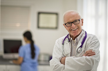 Portrait of a smiling senior doctor standing with his arms folded.