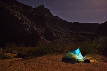 Illuminated tent on the bank of a remote river under a starry sky.