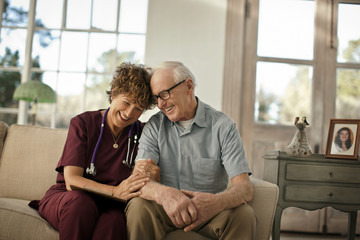 Smiling mature nurse comforting an elderly patient.
