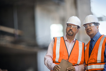 Workers at construction site discuss progress.