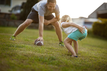 Mid adult man playing American football with his daughter on a lawn.