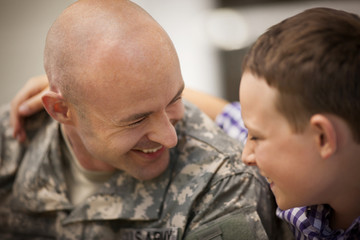 Mid adult man dressed in a military uniform is greeted by his son.