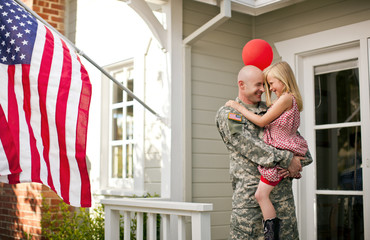 Male soldier hugging his young daughter on the porch of their home.