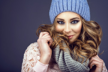 Portrait of young beautiful smiling girl with professional make up and curly hair coming out of her blue knitted hat holding the scarf with her hands. Copy-space. Close up shot