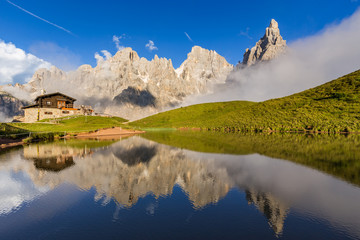 Wall Mural - The Pale di San Martino peaks (Italian Dolomites) reflected in the water, with an alpine chalet on background.