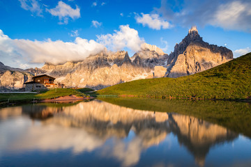Aluminium Prints Reflection The Pale di San Martino peaks (Italian Dolomites) reflected in the water at sunset, with an alpine chalet on background.
