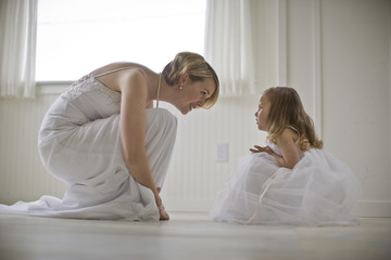 Bride crouching down to face a young flower girl inside a bare room.