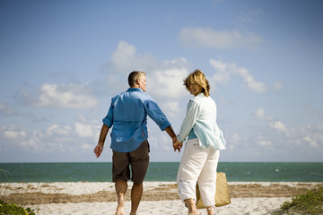 Happy mature couple holding hands while walking together at the beach.
