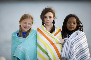 Portrait of three girls standing on a jetty wearing towels.