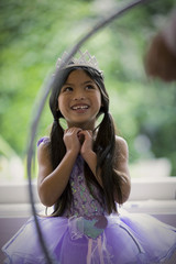 Happy young girl wearing a tiara and a tutu.