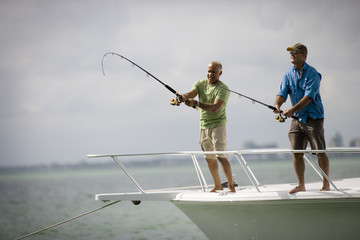 Two smiling mature men fishing off the edge of a boat together in the ocean.
