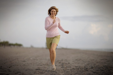 Portrait of a smiling mid-adult woman running along a beach.