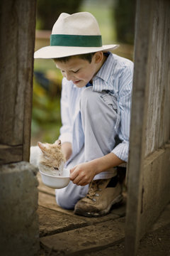 Boy giving a cat some milk from a bowl.