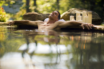 Mid-adult man relaxing in a hot spring.
