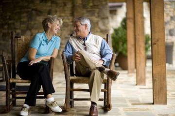 Mature adult couple sitting on a porch talking.