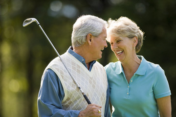 Mature couple laughing while playing golf.