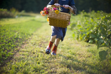 Basket of flowers being held by a young girl running through a field.