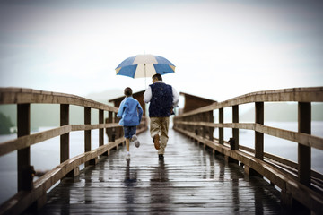 Man holds an umbrella over his young daughter as they run together along a jetty in the rain.