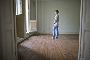 Teenager looking through open doors while standing in a room.