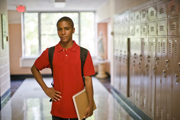 Teenage boy standing in school corridor
