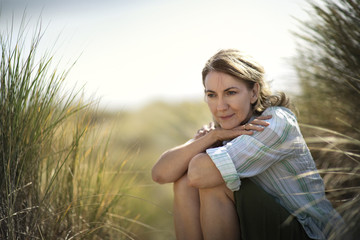 Middle aged woman sitting contemplating at the beach.