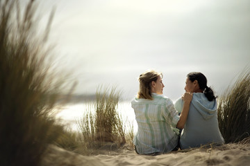 Two friends having a heart-to-heart talk while sitting on the beach.