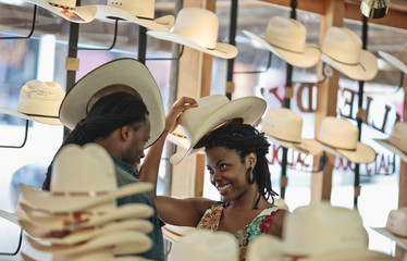 Happy young couple have fun trying on cowboy hats in a hat shop.